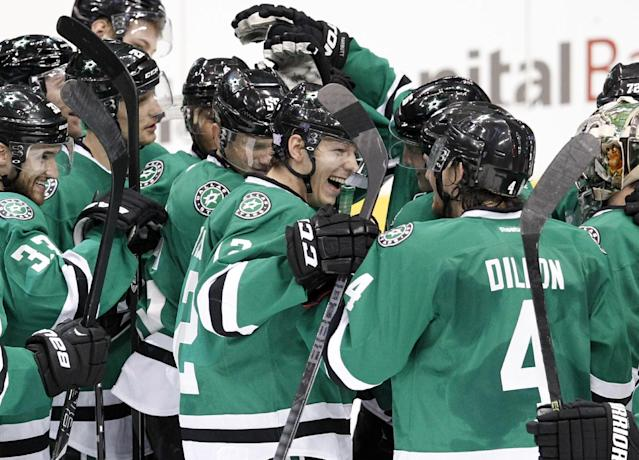 Dallas Stars' Alex Chiasson, center, celebrates with teammates on the ice following after their NHL hockey game against the San Jose Sharks, Thursday, Oct. 17, 2013, in Dallas. Chiasson scored a shootout goal that helped the Stars to the 4-3 win. (AP Photo/Tony Gutierrez)