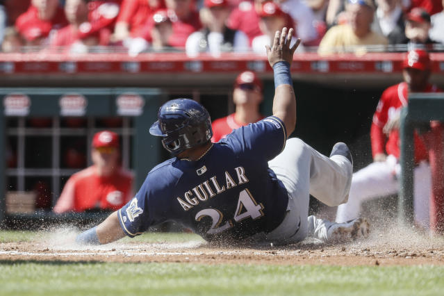 Milwaukee Brewers' Jesus Aguilar slides in to score on an RBI single by Manny Pina off Cincinnati Reds starting pitcher Luis Castillo in the second inning of a baseball game, Wednesday, April 3, 2019, in Cincinnati. (AP Photo/John Minchillo)