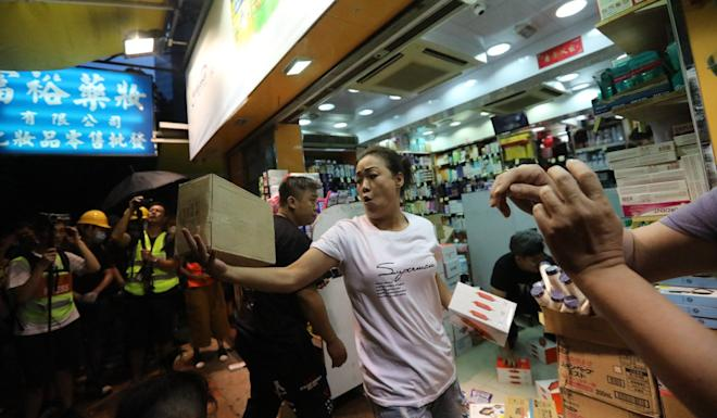 Protesters throw boxes of goods into a Lung Fung Dispensary outlet. Photo: Felix Wong