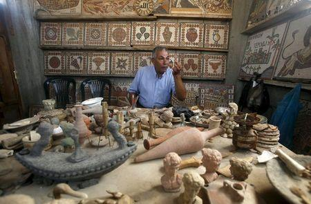 Archeology Nafez Abed sits in front of sculptures and intricate mosaics at his workroom, at Shati refugee camp in Gaza City, November 8, 2015. REUTERS/Suhaib Salem