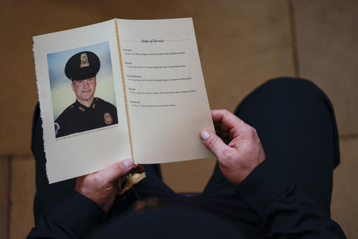FILE - In this Feb. 3, 2021, file photo, a U.S. Capitol Police officer holds a program during a ceremony memorializing U.S. Capitol Police officer Brian Sicknick, as an urn with his cremated remains lies in honor on a black-draped table at the center of the Capitol Rotunda in Washington. The D.C. medical examiner's office says Sicknick, who was injured during the Jan. 6 insurrection, suffered a stroke and ruled the officer died from natural causes. (Demetrius Freeman/The Washington Post via AP, Pool)