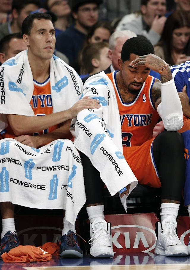 New York Knicks' Pablo Prigioni, left, pats the arm of teammate J.R. Smith, right, late in the second half of an NBA basketball game against the Atlanta Hawks Saturday, Nov. 16, 2013, in New York. Atlanta defeated New York 110-90. (AP Photo/Jason DeCrow)