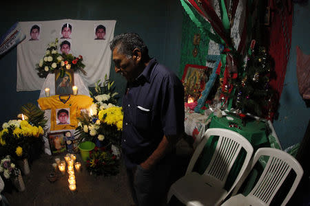 Ezequiel Mora, father of Alexander Mora Venancio stands in front of an altar with pictures of his son at his house in El Pericon, in the southern Mexican state of Guerrero, December 7, 2014. REUTERS/Jorge Dan Lopez