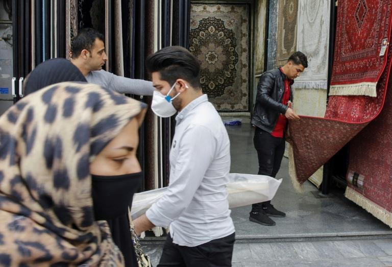 Iranians, some wearing protective masks, pass a carpet shop in the capital Tehran's grand bazaar