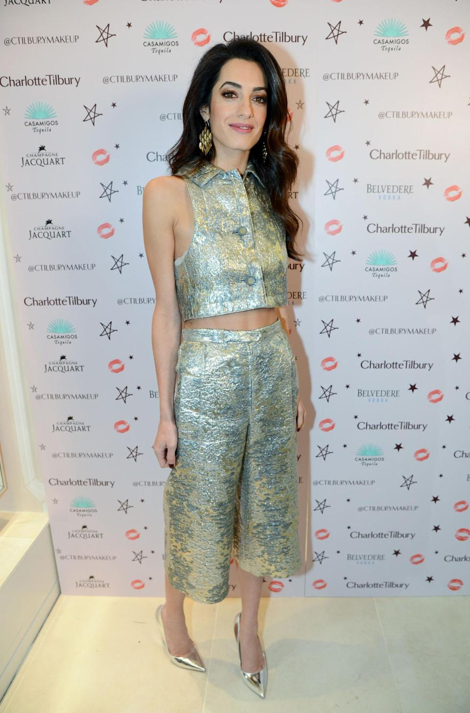 Amal Clooney donned metallic culottes and a matching cropped shirt – showing off her toned tum. The human rights lawyer paired the fashion-forward ensemble with a pair of metallic court shoes and accessorised with a pair of statement earrings. She also had the best date for the night – not her husband George but her mum Baria Alamuddin. [Photo: Rex]