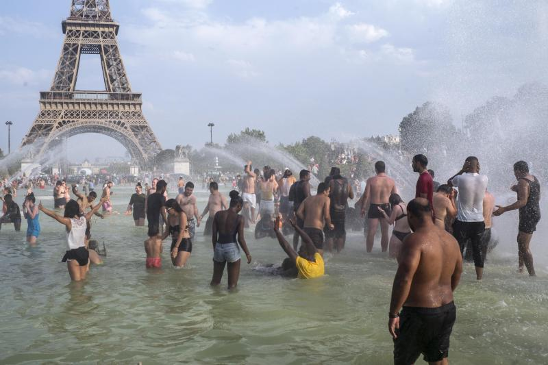 People cool down in the fountains of the Trocadero gardens in Paris, Thursday July 25, 2019, when a new all-time high temperature of 42.6 degrees Celsius (108.7 F) hit the French capital. in the background is the Eiffel Tower. (AP Photo/Rafael Yaghobzadeh)
