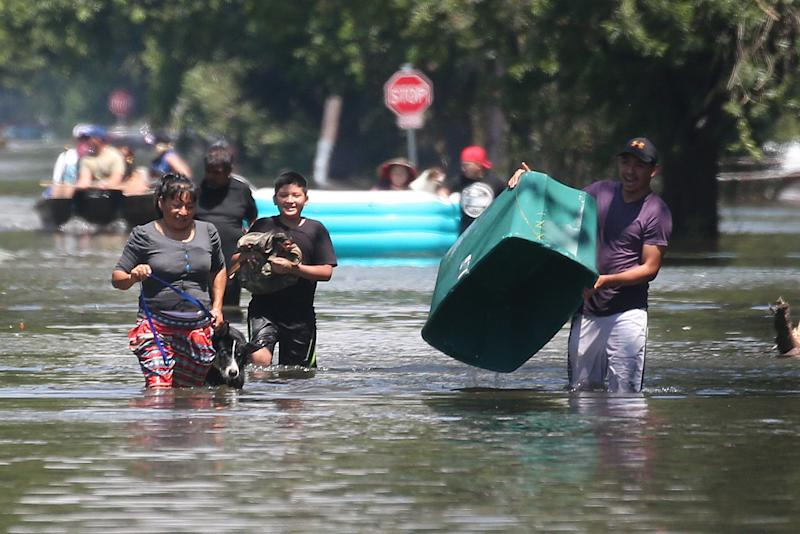 People walk with their possessions out of a flooded area of Port Arthur, Texas on Aug.31, 2017. (Carlo Allegri / Reuters)