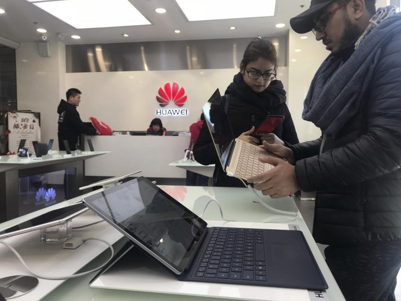 Foreigners look at a Huawei computer at a Huawei store in Beijing, China, Thursday, Dec. 6, 2018. Canadian authorities said Wednesday that they have arrested the chief financial officer of China's Huawei Technologies for possible extradition to the United States. (AP Photo/Ng Han Guan)