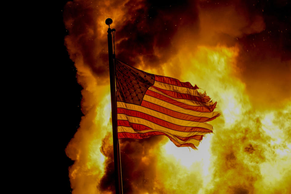 A flag flies over a department of corrections building ablaze during protests on Monday, in Wisconsin unrest. Source: AP