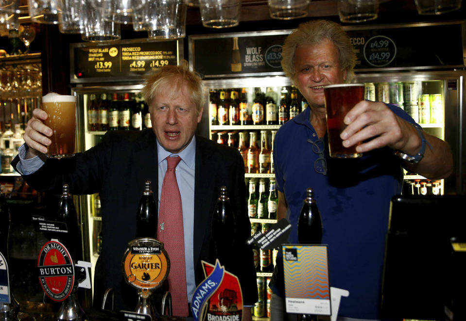 Conservative Party leadership candidate Boris Johnson gestures with Tim Martin, Chairman of JD Wetherspoon,  during a visit to Wetherspoons Metropolitan Bar in London, Wednesday July 10, 2019. (Henry Nicholls/Pool Photo via AP)