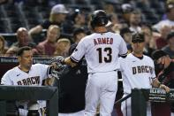 Arizona Diamondbacks' Nick Ahmed (13) celebrates his run scored against the Milwaukee Brewers with teammate Asdrubal Cabrera, left, and manager Torey Lovullo, right, during the second inning of a baseball game Monday, June 21, 2021, in Phoenix. (AP Photo/Ross D. Franklin)