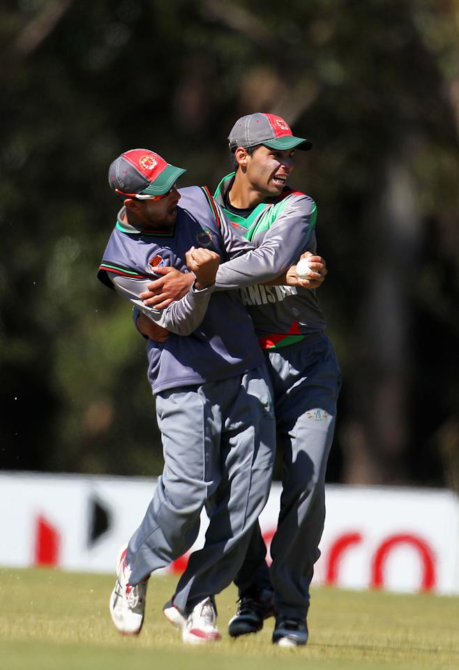 SUNSHINE COAST, AUSTRALIA - AUGUST 11:  Mohammad Jawed of Afghanistan (L) celebrates with a team mate after catching out Saad Ali of Pakistan during the ICC U19 Cricket World Cup 2012 match between Pakistan and Afghanistan at John Blanck Oval on August 11, 2012 in Sunshine Coast, Australia.  (Photo by Graham Denholm-ICC/Getty Images)