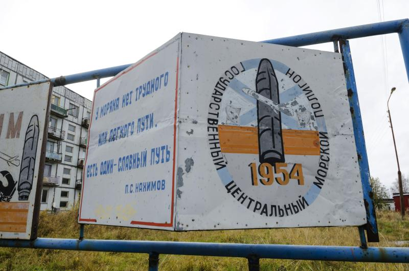 "This photo taken on Oct. 7, 2018, shows a billboard that reads ""The State Central Navy Testing Range"" near residential buildings in the village of Nyonoksa, northwestern Russia. The Aug. 8, 2019, explosion of a rocket engine at the Russian navy's testing range just outside Nyonoksa led to a brief spike in radiation levels and raised new questions about prospective Russian weapons. (AP Photo/Sergei Yakovlev)"