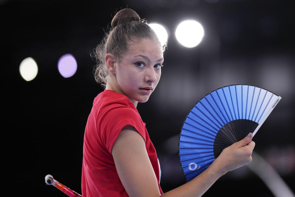 Evita Griskenas from the United States uses a hand fan during a break of her individual rhythmic gymnastics training session at the 2020 Summer Olympics, Thursday, Aug. 5, 2021, in Tokyo, Japan. (AP Photo/Markus Schreiber)