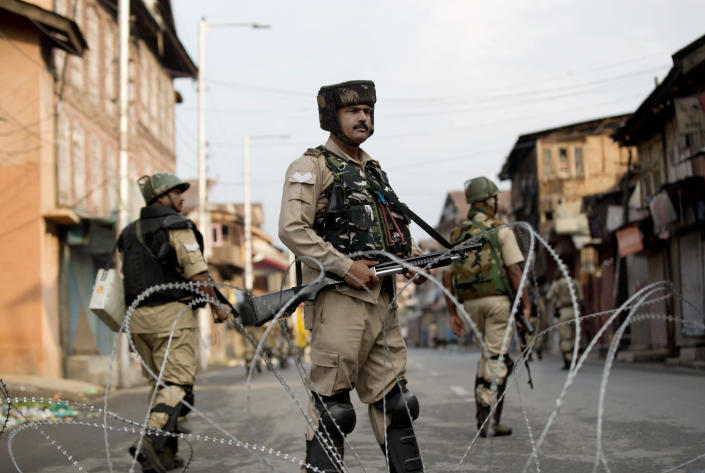 Indian Paramilitary soldiers stand guard during curfew in Srinagar, Indian controlled Kashmir, Wednesday, Aug. 7, 2019. Authorities in Hindu-majority India clamped a complete shutdown on Kashmir as they scrapped the Muslim-majority state's special status, including exclusive hereditary rights and a separate constitution, and divided it into two territories. (AP Photo/Dar Yasin)