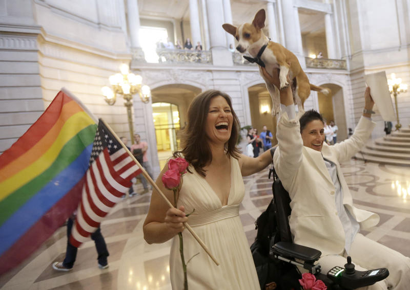 "Jen Rainin, left, laughs as her wife Frances holds up their dog Punum after they were married at City Hall in San Francisco, Friday, June 28, 2013. A three-judge panel of the 9th U.S. Circuit Court of Appeals issued a brief order Friday afternoon dissolving, ""effective immediately,"" a stay it imposed on gay marriages while the lawsuit challenging the ban advanced through the courts. (AP Photo/Jeff Chiu)"