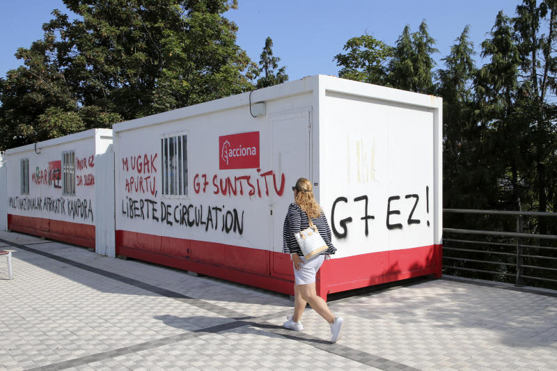 """A woman walks past graffitis reading in Basque language """"No to G7"""" Wednesday, Aug. 21, 2019 in Irun, Spain. Protesters are setting up camp in towns near the Spanish border to prepare actions during the Aug. 24-26 gathering of major world democracies. (AP Photo/Bob Edme)"""
