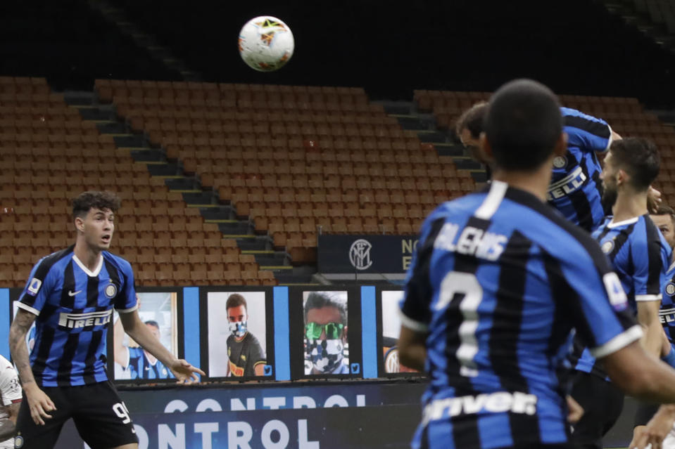 Inter Milan's Diego Godin, rear right, scores his side's second goal during a Serie A soccer match between Inter Milan and Torino, at the San Siro stadium in Milan, Italy, Monday, July 13, 2020. (AP Photo/Luca Bruno