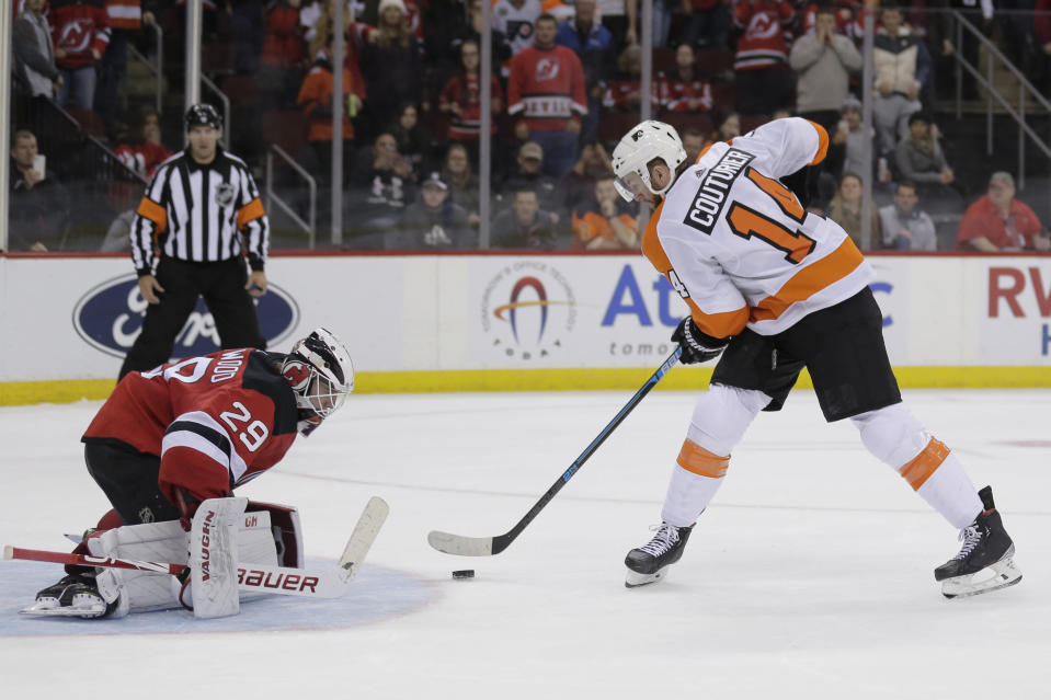 Philadelphia Flyers' Sean Couturier, right, scores past New Jersey Devils goaltender Mackenzie Blackwood during the shootout in an NHL hockey game in Newark, N.J., Friday, Nov. 1, 2019. The Flyers won 4-3. (AP Photo/Seth Wenig)