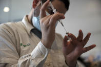 A medical worker prepares a vial of the Pfizer coronavirus vaccine at Clalit Health Service's center in the Cinema City complex in Jerusalem, Wednesday, Sept. 22, 2021. Israel is pressing ahead with its aggressive campaign of offering coronavirus boosters to almost anyone over 12 and says its approach was further vindicated by a U.S. decision to give the shots to older patients or those at higher risk. (AP Photo/Maya Alleruzzo)
