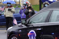 """A woman, center, places her hand on her chest as a hearse carrying the coffin of the late U.S. Capitol Police officer William """"Billy"""" Evans, right, drives though downtown Adams, Mass., following a funeral Mass for Evans, Thursday, April 15, 2021. Evans, a member of the U.S. Capitol Police, was killed on Friday, April 2, when a driver slammed his car into a checkpoint he was guarding at the Capitol. (AP Photo/Steven Senne)"""