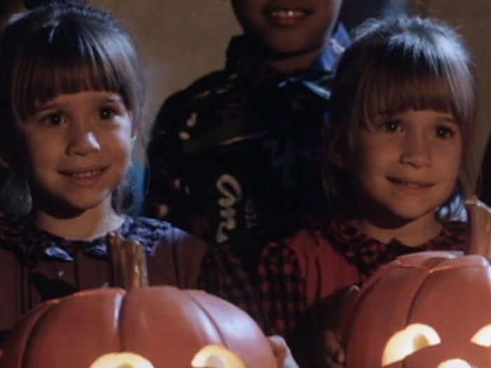 young Mary-Kate and Ashley Olsen holding pumpkins