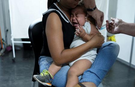 A Venezuelan woman holds her son as he receives a free vaccination given by a volunteer, after showing their passports or identity cards at the Pacaraima border control, Roraima state, Brazil August 8, 2018. Picture taken August 8, 2018.  REUTERS/Nacho Doce