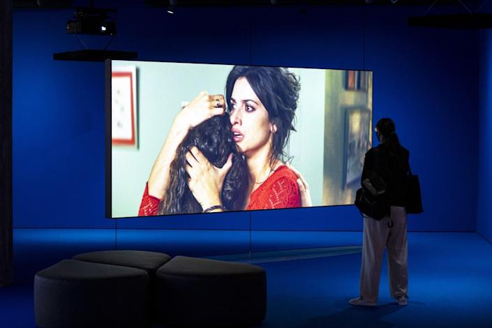 A visitor watches a movie play on a large screen