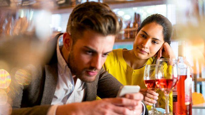 A couple are out having drinks and the woman looks irritated that her partner is on his mobile phone and not paying her any attention.