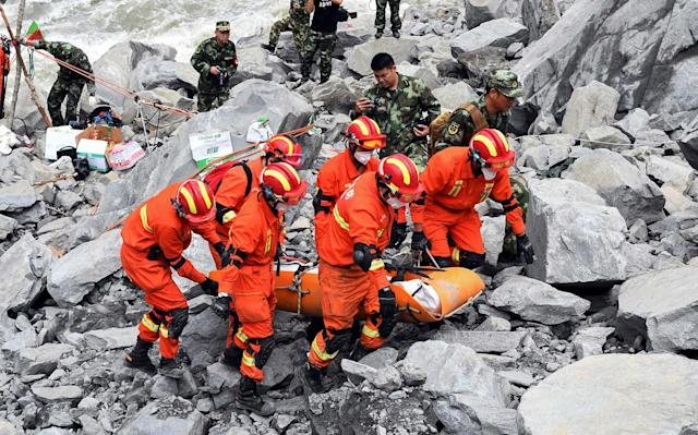 <p>Rescue workers evacuate a body from the site of a landslide in the village of Xinmo, Mao County, Sichuan Province, China, June 25, 2017. (Photo: CNS/An Yuan via Reuters) </p>