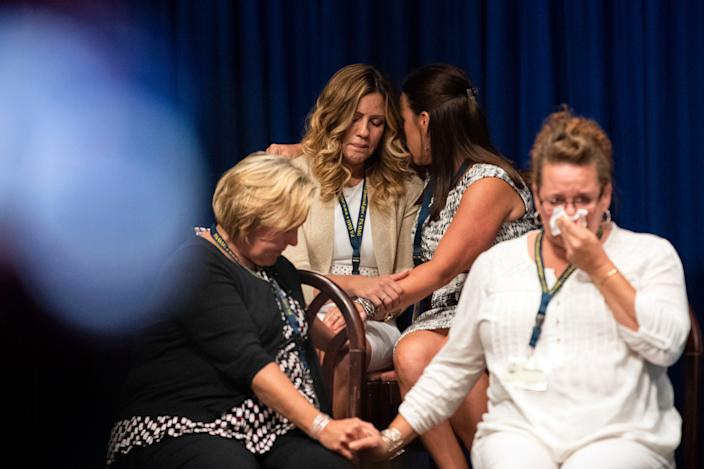 Survivors comfort each other while Pennsylvania Attorney General Josh Shapiro outlined the findings of the grand jury investigation into six Catholic dioceses in the state Aug. 14, 2018. The grand jury's report detailed child sexual abuse and cover-up by more than 300 clergy.