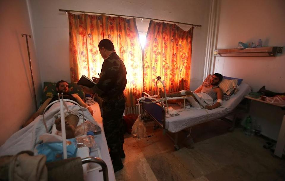 Syrian men, who escaped an attack by Islamist fighters on a medical facility, lay in bed at a hospital in Latakia, a coastal city controlled by the regime, on May 26, 2015 (AFP Photo/Youssef Karwashan)