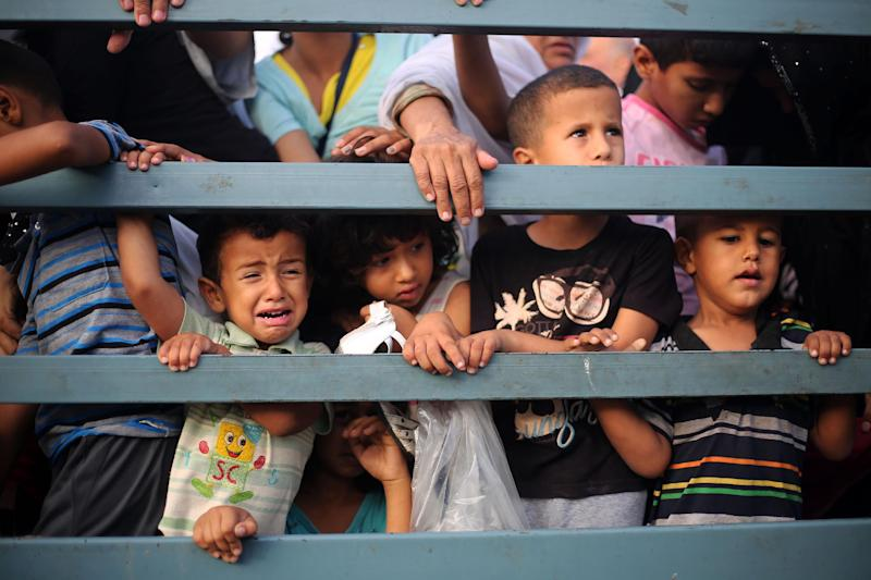 Palestinian children leave their neighborhoods to safer locations amid continuing Israeli bombardment of Khan Yunis in the southern Gaza Strip, on July 24, 2014