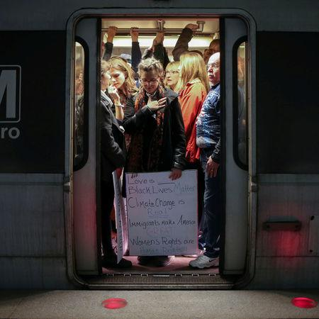 A woman holds a placard while taking a Metrorail en route to the Women's March, planned in opposition to the agenda and rhetoric of President Donald Trump, in Washington, D.C., U.S. on January 21, 2017. REUTERS/Adrees Latif
