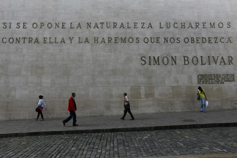 """People walk past a quote by Simon Bolivar that reads in Spanish: """"If nature opposes, we will fight against her and make her obey us,"""" near the National Assembly in Caracas, Venezuela, Wednesday, Jan. 15, 2020. There is a struggle for control of the opposition-dominated National Assembly and Venezuela as a whole, a nation suffering economic and social collapse that's led an estimated 4.5 million to emigrate. (AP Photo/Ernesto Vargas)"""