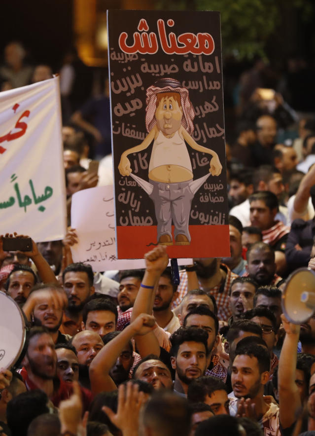 <p>Demonstrators hold up posters in front of Jordanian policemen during a protest near the prime minister's office in Amman, Jordan, on June 6, 2018. Jordanian Prime Minister Hani Mulki resigned on June 4 after a wave of anti-austerity protests by citizens suffering from high unemployment and repeated price hikes. (Photo: Ahmad Gharabli/AFP/Getty Images) </p>