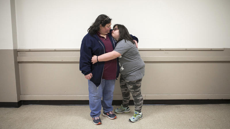 Marjorie Guldan and her daughter Rebecca, 14, hug after the Deer Park 4-H Club holiday party.