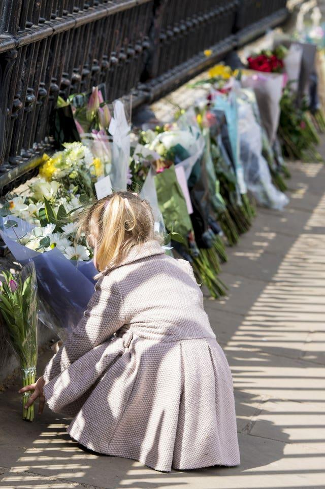Two-year-old Maggie lays a floral tribute outside Buckingham Palace