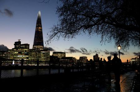 FILE PHOTO: People walk alongside the Thames as the sun sets behind The Shard in London, Britain, December 3, 2018. REUTERS/Simon Dawson/File Photo