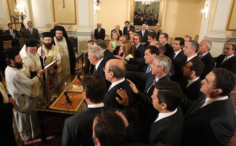 Greece's new Cabinet ministers take the oath of office during a ceremony officiated by Greece's Orthodox Archbishop Ieronimos, 2nd left, at the Presidential palace in Athens, Tuesday, June 25, 2013. Greece's new cabinet was sworn in Tuesday after a broad reshuffle in which conservative Prime Minister Antonis Samaras handed key posts to the coalition government's minority Socialist party following a political crisis. (AP Photo/Thanassis Stavrakis)
