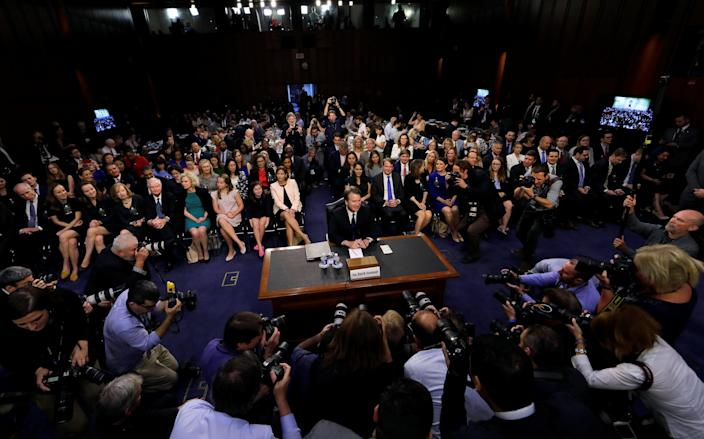 Supreme Court nominee Brett Kavanaugh is surrounded by photographers as he takes his seat for his Senate Judiciary Committee confirmation hearing on Capitol Hill in Washington, D.C., on Tuesday. (Jim Bourg/Reuters)