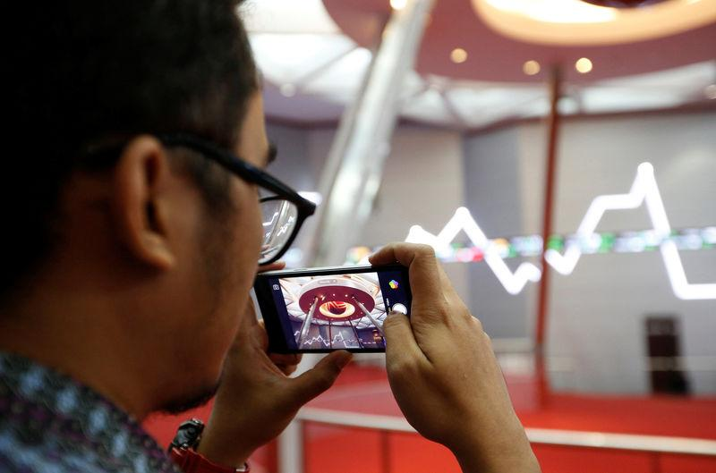 A man takes pictures inside the Indonesia Stock Exchange building in Jakarta, Indonesia, September 6, 2018. REUTERS/Willy Kurniawan/Files