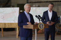 """FILE - In this Sept. 13, 2021, file photo President Joe Biden speaks about recent wildfires, at Sacramento Mather Airport in Mather, Calif., as California Gov. Gavin Newsom listens. Surveying damage from California wildfires to hurricane-induced flooding in Louisiana and New York Biden said America must get serious about the """"code red"""" danger posed by global warming. (AP Photo/Evan Vucci, File)"""