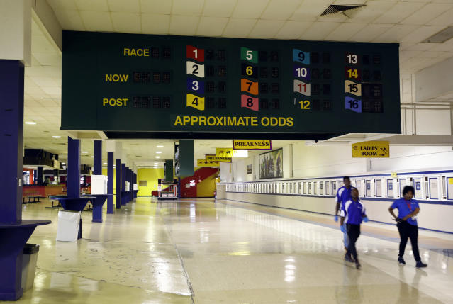 People walk down a concourse at Pimlico Race Course as preparations take place for the Preakness Stakes horse race, Tuesday, May 15, 2018, in Baltimore. Old Hilltop is showing its age, and it will cost an estimated $300 million to make it right. (AP Photo/Patrick Semansky)