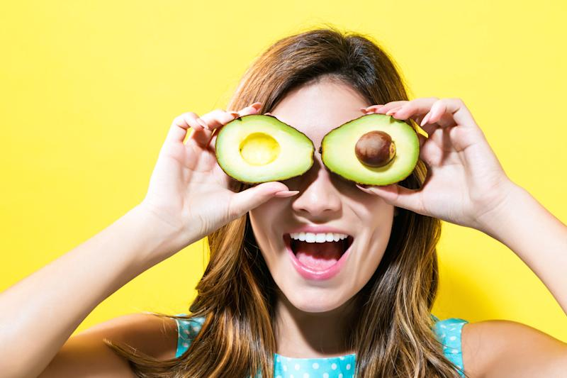 Happy young woman holding avocado halves on a yellow background.