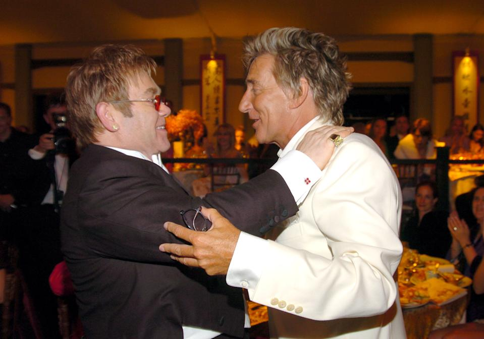 Sir Elton John and Rod Stewart. Sir Elton John has chosen to wear an emerald cut yellow diamond stud and an 42 ct emerald cut yellow diamond ring, as well as the Jumbo Happy Spirit pendant set with diamonds. (Photo by KMazur/WireImage for Chopard )