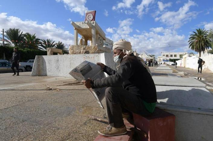 A Tunisian man reads a newspaper in front of a statue to Mohamed Bouazizi, the man whose protest kickstarted revolution a decade ago; Tunisia today remains beset by challenges