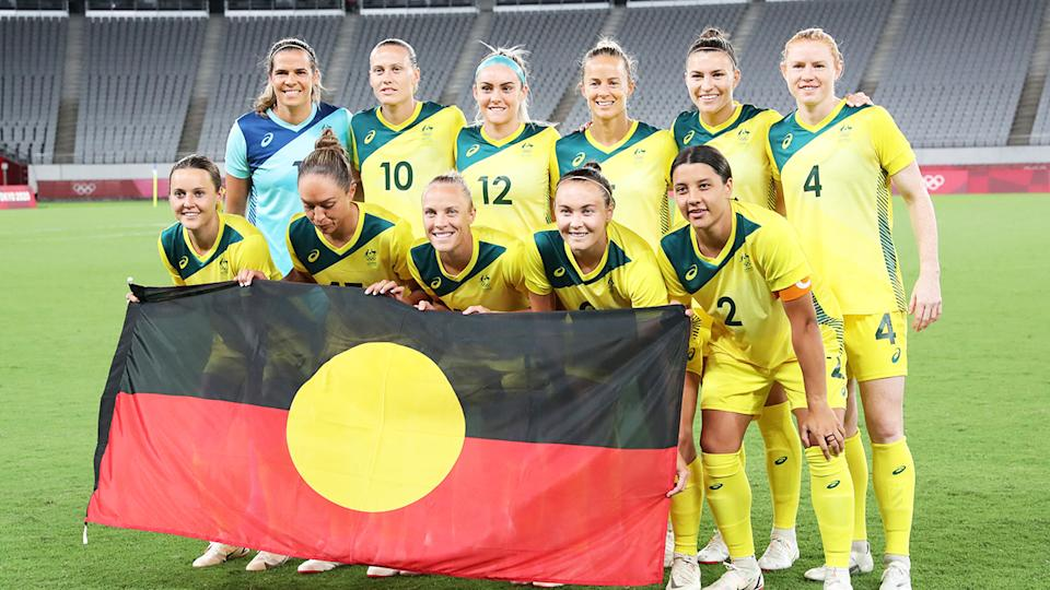 The Matildas holding the Aboriginal Flag  and posing for a photo ahead of their opening match at the Tokyo Olympic Games.