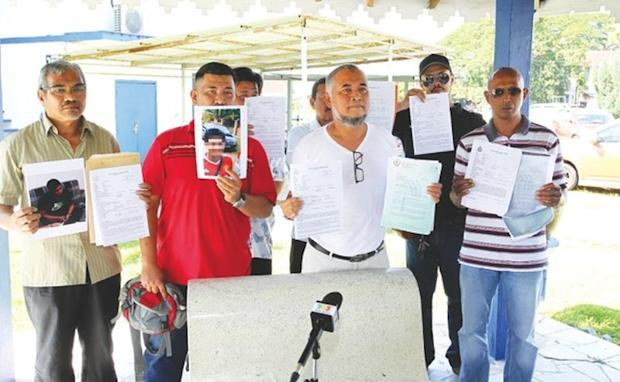 Aznul (holding photograph of 'Faiz'), Safaruddin (centre) and other contractors who lodged reports at the Sungai Senam police station yesterday. — Picture by Farhan Najib