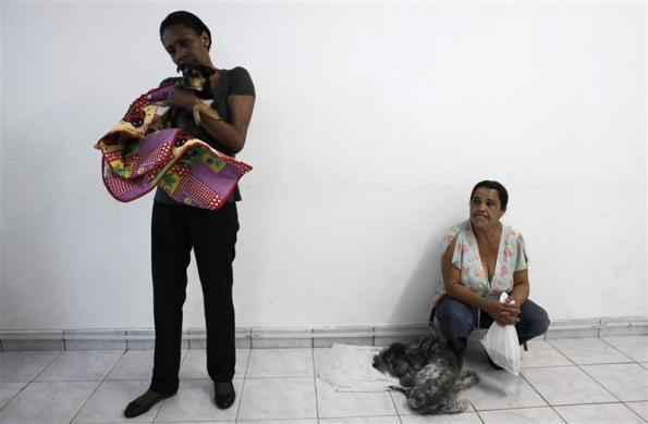 Women wait with their dogs for medical examinations in the Anclivepa-SP veterinarian hospital in Sao Paulo August 22, 2012.